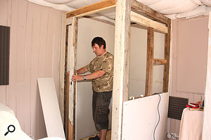 Paul stands inside the part‑constructed vocal booth.