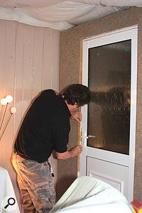 Paul fits the architrave around the aluminium door.