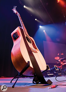 Acoustic guitar on stand on stage.