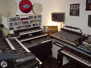 James's area of the studio. Instruments, from left, include Roland JP8000 and Korg N364 synths, Roland Handsonic percussion controller, XP30 keyboard, MC505 groovebox and SH101 analogue synth, harmonium, Korg Electribe groovebox and Sequential Prophet 5 synth.
