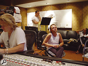 Metallica get busy in the control room: drummer Lars Ulrich (centre right) looks thoughtful while singer James Hetfield (centre left) works on a St. Anger lyric. Bob Rock attends to the desk while Kirk Hammett looks on.