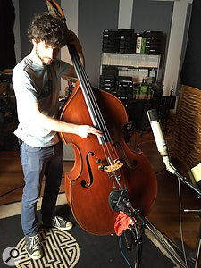 Michael League tracks an upright bass part, miked with a  Telefunken ELA M251 above the instrument, a  Coles 4038 in front and an AKG C451 wedged into the bridge. All three mics were used in the mix.
