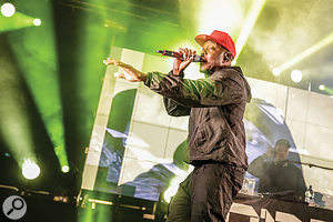 Dizzee Rascal performs in front of an LED wall.