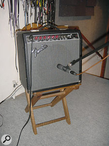 Miking up a guitar amp. The mic should be a dynamic model placed close to the grille cloth. For a less bright sound, point the mic further towards the edge of the speaker cone.