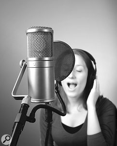 Girl with headphones singing into large condenser mic.