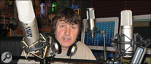 Paul White in his studio with multiple microphones.