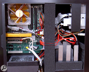 Here you can see the unusual interior of the PaQ case, where most of the interior components are a tight press-fit into high-absorption acoustic foam. Towards the rear of the case (the left in this photograph) the motherboard assembly slides into grooves in the case, while beneath the central vertical strip hide three 120mm case fans running in parallel. At top right the optical and floppy drives are a firm push-fit between foam spacers, and at lower right you can see the aluminium heat spreaders that house up to three hard drives, as well as the perforations of the muffler (part of the front door's acoustic labyrinth).