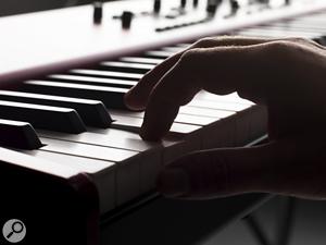 Finger on piano keyboard.