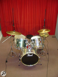 If you're recording a drummer who hits his or her cymbals too hard, conventional overhead-mic positioning (left) can make the problem worse, because the cymbals are physically closer to the mics than the drums are, and they send most of their sound along their vertical axis anyway. The right-hand picture shows an alternative setup where the the mics are now closer to the drums and roughly on the plane of the cymbals. The situation has also been improved further by pulling a curtain across the wall, increasing high-frequency absorption, and by using cardioid mics pointed towards the snare drum so that they pick up the off-axis cymbals less brightly.