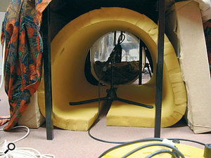 Getting a tight kick sound in a small school studio without much acoustic treatment can be tricky, and one approach is to try to isolate the kick‑drum mic as much as possible from the room. If you want to mic from a little way away from the drum, the best way to achieve this isolation is to build a thick‑walled tunnel out in front of the kick drum and surrounding the mic. Here you can see down one such tunnel Mike put together in a school studio recently, using a small desk as support. At the far end is the kick drum with its resonant head removed.