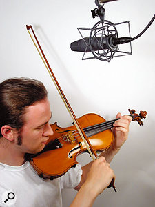 When multitracking a single violin or viola to sound like a full section, using different miking positions for the various parts and takes will add some tonal variation. Placing the mic at least 12 inches away will ensure that you pick up plenty of room sound, adding further variety.