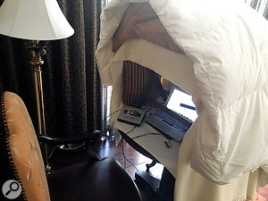 Joe Cipriano uses a luggage rack or ironing board as the frame for his hotel voiceover booths. He positions this frame on a desk or bureau, drapes blankets or a duvet over the top, stuffs pillows inside, and leaves enough space for his laptop, interface and directional microphone.