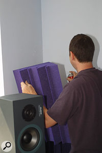 Hugh installs the newly made wall panels, using a spirit level for a neat result, while Paul carefully sticks acoustic foam bass traps directly into the front corners of the room using more spray adhesive.