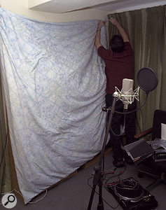 With the studio workstation set up at one end of the room, a corner at the other end was now set up as a vocal recording area. In order to reduce the amount of room sound reaching the vocal mic, Paul closed the heavy bay-window curtain and also deadened the wall by hanging a double duvet between the two windows — the existing curtain rails made convenient fixing points.