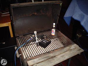 Another way to get a novel guitar sound: the mic is taped to a barbeque grille and a miniature amp is rested on it.