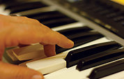 Passing Chords: fingers on piano keys.